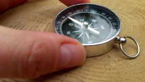 人的手和采取指南针确定世界的方向在大麻木头,特写镜头背景的  股票视频
