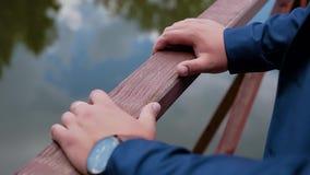 人的手在一个小木桥的扶手栏杆说谎在池塘的 股票录像