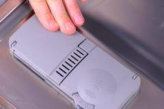 人的手在洗碗机的自动隔间投入洗涤剂片剂 库存图片