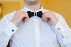 人的手在衣服的接触弓领带 免版税图库摄影