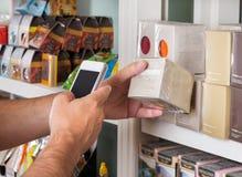 人的手扫描产品通过手机 免版税库存照片