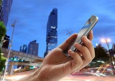 人的手拿着在摩天大楼城市背景的一个智能手机和 免版税库存图片