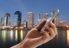 人的手拿着在暮色ba摩天大楼城市的一个智能手机 免版税库存图片