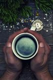 人的手拿着地球由一点bitcoin和欢乐云杉分支反射的一个杯子咖啡 概念o 免版税库存照片
