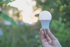 人的手拿着想法或成功的电灯泡或者太阳 库存照片