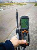 人的手拿着测量的温度和湿气一个设备 在街道上的措施 免版税库存照片