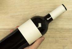 年轻人的手拿着红葡萄酒瓶在轻的木背景 免版税库存图片