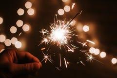 人的手拿着闪烁发光物,新年快乐 免版税库存图片