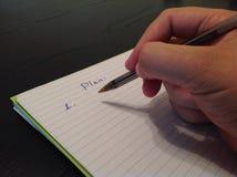 人的手文字在纸板料的计划标题 免版税库存照片