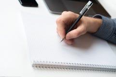 人的手文字特写镜头在纸的 与笔记本,膝上型计算机,电话的白色桌 免版税库存图片