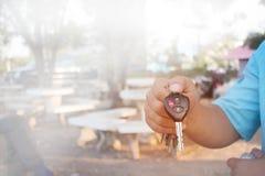 人的手显示与打开标志和警报的汽车钥匙 免版税库存照片
