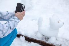 人的手照片雪人在手机的狗在公园在冬天 免版税库存照片