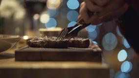 人的手特写镜头有切在木板的叉子和刀子的鲜美牛排在餐馆 r ?? 股票视频