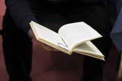 人的手特写镜头黑暗的衣裳的有开放书的 真正的场面在商店 自学,教育,指南 免版税库存图片
