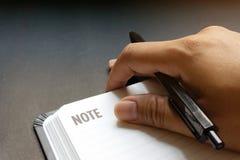 人的手的关闭有写某事的黑笔的在空白行笔记本有黑书桌背景在剧烈的点燃的口气 免版税图库摄影