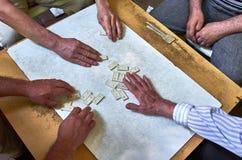 人的手的顶视图演奏多米诺的 库存图片