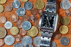 人的手表和金属硬币 免版税库存图片
