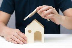 人的手设法保护木玩具房子 免版税库存图片