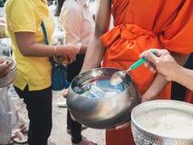 人的手,当对修士` s施舍的被投入的食物在最后佛教被借的天时的滚保龄球 免版税图库摄影