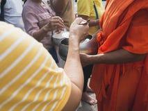 人的手,当对和尚` s施舍的被投入的食物在最后佛教被借的天时的滚保龄球 库存照片