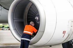 人的技术员工程师在远航以后检查涡轮发动机` s飞机在停车处的刀片和psodki在机场 库存照片