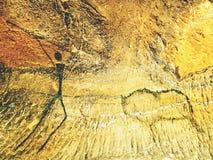 人的狩猎油漆在砂岩墙壁,史前图片上的 在砂岩洞的黑抽象派 库存图片