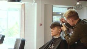 人的美发师 薄饼 在年轻人` s头一边的头发切口有头发剪刀的 影视素材