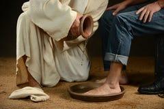人的耶稣洗涤的脚牛仔裤的 图库摄影