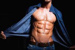 年轻人的肌肉和性感的身体牛仔裤衬衣的 库存照片