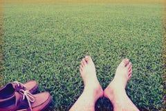 人的脚在豪华的绿草背景,葡萄酒样式的ans鞋子 免版税库存图片