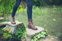 年轻人的脚垫脚石的在池塘 免版税库存图片