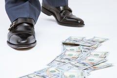 人的脚站立在金钱轨道附近的黑鞋子的 库存图片