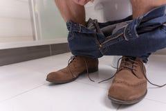 人的腿坐一个马桶在卫生间里 图库摄影