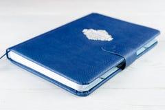 人的蓝色皮革笔记本白色木背景的,精选 免版税图库摄影