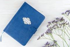 人的蓝色皮革笔记本白色木背景的 名列前茅vi 免版税库存图片