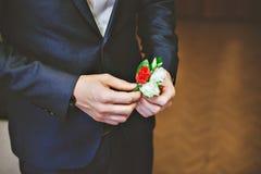 人的蓝色衣服,红色领带,白色衬衣 新郎调整玫瑰他的钮扣眼上插的花  库存照片