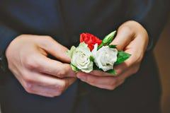 人的蓝色衣服,红色领带,白色衬衣 新郎调整玫瑰他的钮扣眼上插的花  免版税图库摄影