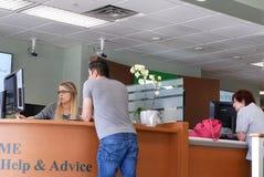 人的行动谈话与出纳在TD里面的服务计数器开户 免版税库存照片