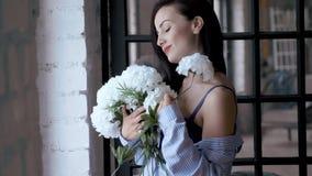 人的衬衣和胸罩立场的美丽的年轻女人与白花花束在窗口附近的 股票录像