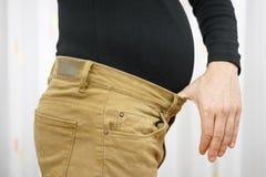 人的裤子太紧归结于高重量 免版税库存照片