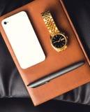 人的辅助部件、金黄手表、笔和手机在皮革日志 库存图片