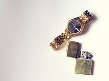 人的辅助部件、金黄手表和打火机在白色 库存图片