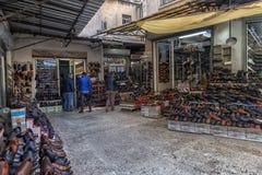 人的鞋子、许多小商店和柜台在街道上在旁边 库存照片