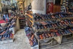 人的鞋子、许多小商店和柜台在街道上在旁边 免版税库存照片