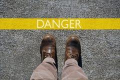 人的鞋子用您的文本的拷贝空间从上面观看,词危险和一条黄色界限线 免版税图库摄影