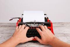 人的顶视图和有白色白纸的红色老打字机在灰色桌上覆盖 免版税库存照片