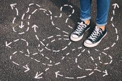 人的顶视图图象站立在有显示不同的方向的被绘的箭头的柏油路的牛仔裤和减速火箭的鞋子的 库存照片
