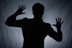 人的阴影在黑暗的织品后的 免版税库存照片