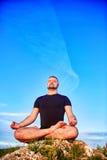 人的画象坐在莲花坐的一个岩石反对蓝天 免版税库存照片