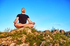 人的画象坐在莲花坐的一个岩石反对蓝天 免版税图库摄影